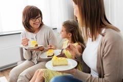 Moder, dotter och farmor som äter kakan arkivbilder