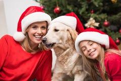 Moder, dotter och hund i jultomtenhattar Royaltyfria Bilder