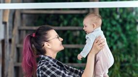 Moder för lycklig hipster för sidosikt som ung spelar med den lilla sonen som beundrar och kysser honom medelcloseup lager videofilmer