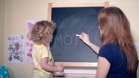 Moder för ord för handstil för kvinnamoder- och flickadotter med krita på svart bräde arkivfilmer