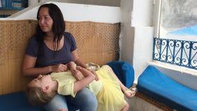 Moder för ung kvinna som slår den sjuka magedottern som ligger på hennes varv arkivfilmer