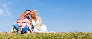 Moder fader, barn som sitter i öppen luft Fotografering för Bildbyråer