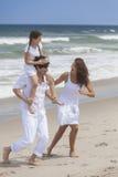 Moder-, fader- & barnfamilj som leker på stranden Royaltyfri Foto