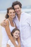 Moder-, fader- och barnfamilj som är lycklig på strand Arkivbild