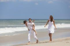 Moder-, fader- och barnfamiljspring som har gyckel på stranden Arkivbilder