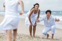 Moder-, fader- och barnfamiljspring som har gyckel på stranden Fotografering för Bildbyråer