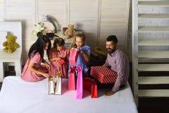 Moder, fader och d?ttrar med shoppingp?sar och packar royaltyfri fotografi