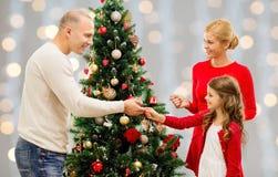 Moder, fader och dotter på julträdet arkivfoto
