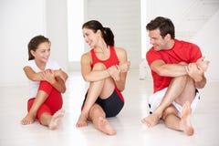 Moder, fader och dotter som gör yoga Royaltyfria Bilder