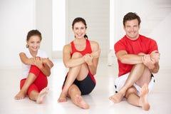 Moder, fader och dotter som gör yoga Arkivfoto