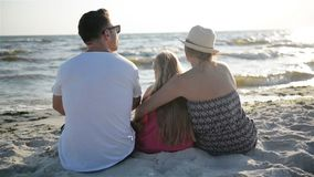 Moder-, fader- och dottersammanträde på stranden nära havet och att krama att se på solen och vågorna stock video
