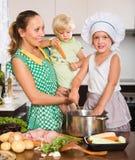 Moder med att laga mat för två döttrar Fotografering för Bildbyråer