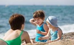 Moder med barn på stranden Arkivfoton