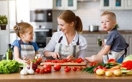 Moder med barn som f?rbereder gr?nsaksallad royaltyfri foto
