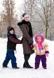 Moder med barn som kopplar av på snow royaltyfria bilder
