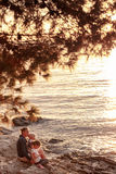 Moder med barn som sitter på stranden, hållande ögonen på solnedgång Royaltyfri Foto