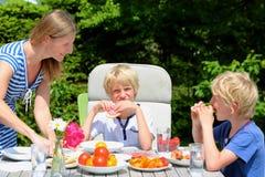 Moder med barn som utomhus äter royaltyfri bild