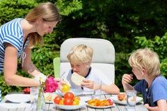 Moder med barn som utomhus äter royaltyfria foton