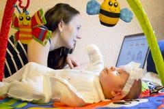 Moder med barnet på datoren arkivfoto