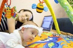 Moder med barnet på datoren Arkivbild