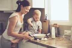 Moder med barnet som tillsammans lagar mat Arkivfoton