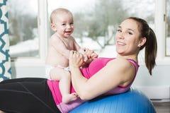 Moder med barnpojken som gör konditionövningar fotografering för bildbyråer
