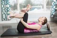 Moder med barnpojken som gör konditionövningar royaltyfria bilder
