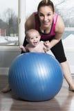 Moder med barnpojken som gör konditionövningar arkivbilder