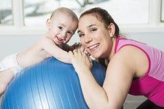 Moder med barnpojken som gör konditionövningar royaltyfri foto