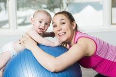 Moder med barnpojken som gör konditionövningar royaltyfri fotografi