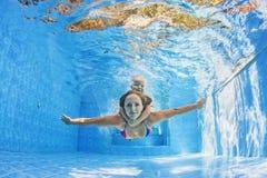 Moder med barnsimning och dykning som är undervattens- i pöl Arkivfoton