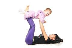 Moder med behandla som ett barn som gör övningar över vit Royaltyfria Bilder