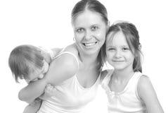Moder med döttrar som isoleras på vit Arkivbild