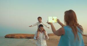 Moder med den blockskyttefadern och sonen på stranden arkivfilmer