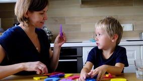 Moder med den förskole- pojken som lär engelskt alfabet och nummer arkivfilmer