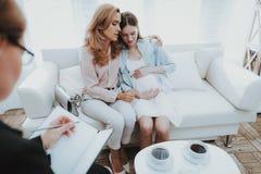 Moder med den gravida dottern i doktor Office fotografering för bildbyråer
