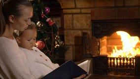 Moder med den lilla dotterläseboken nära spisen och julträd arkivfilmer