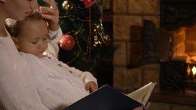 Moder med den lilla dotterläseboken nära spisen och julträd stock video