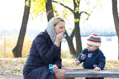 Moder med den lilla sonen som blåser bubblor Arkivfoto