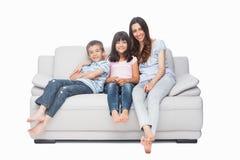 Moder med deras barn som sitter på soffan Fotografering för Bildbyråer