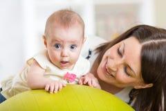 Moder med det lilla barnet som gör övningar med den gymnastiska bollen Begrepp av att att bry sig för baby'sens hälsa Arkivbilder