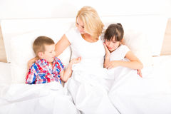 Moder med dottern och sonen som kopplar av i säng Royaltyfria Bilder
