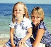 Moder med dottern på havet som tillsammans kostas, lycklig verklig familjsmi royaltyfria foton