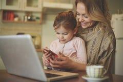 Moder med dottern som använder mobiltelefonen fotografering för bildbyråer