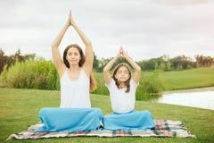 Moder med dottern som gör yogaövning Arkivbild