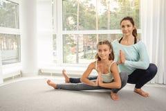 Moder med dottern som gör yogaövning arkivbilder