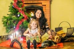 Moder med en dotter och en liten hund Askar av gåvor på lodisarna fotografering för bildbyråer