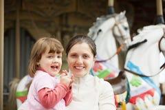 Moder med flickan mot karusell Royaltyfri Fotografi