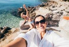 Moder med fotoet för selfie för sontagandesemester i Adriatiskt havfjärd Royaltyfri Foto