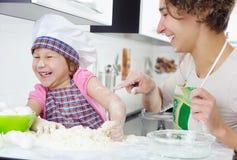 Moder med glad matlagning för dotter fotografering för bildbyråer